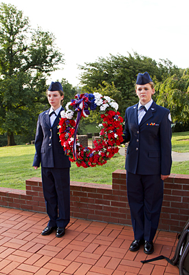 Two military school students prepare to lay the wreath at the base of the flag.