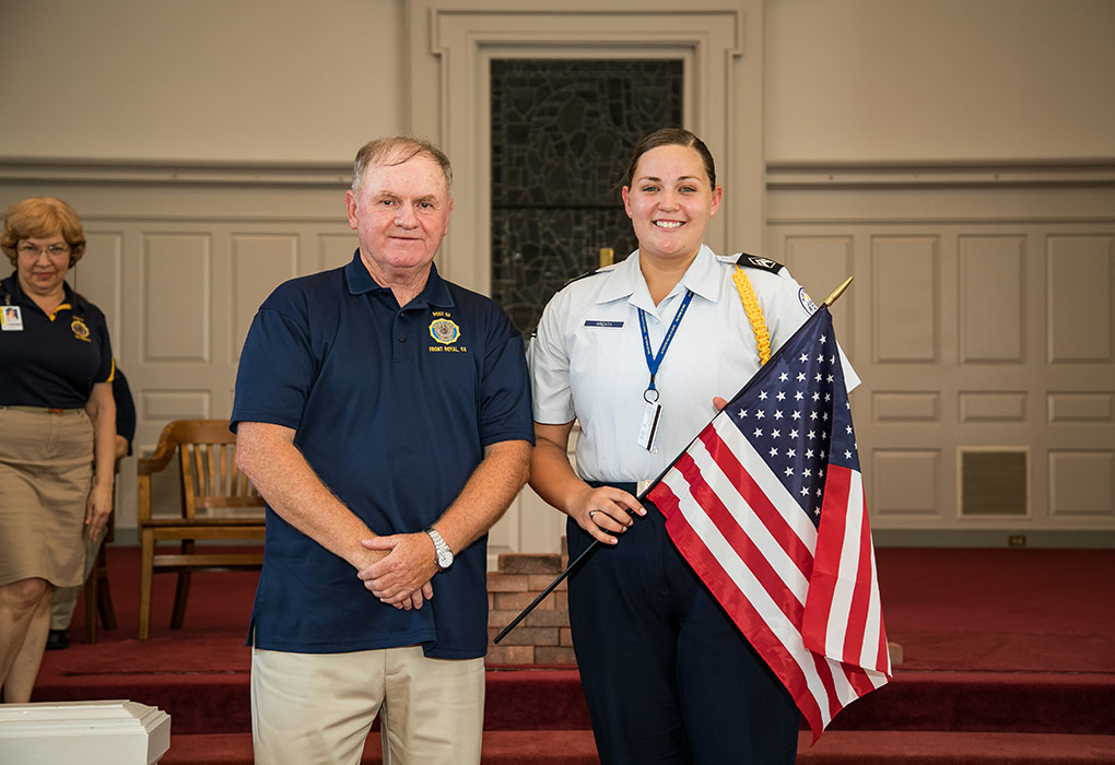 Mr. Rick Kinsey, Commander of American Legion Post 53, presents a flag to R-MA Group Commander Taylor Wreath '20.