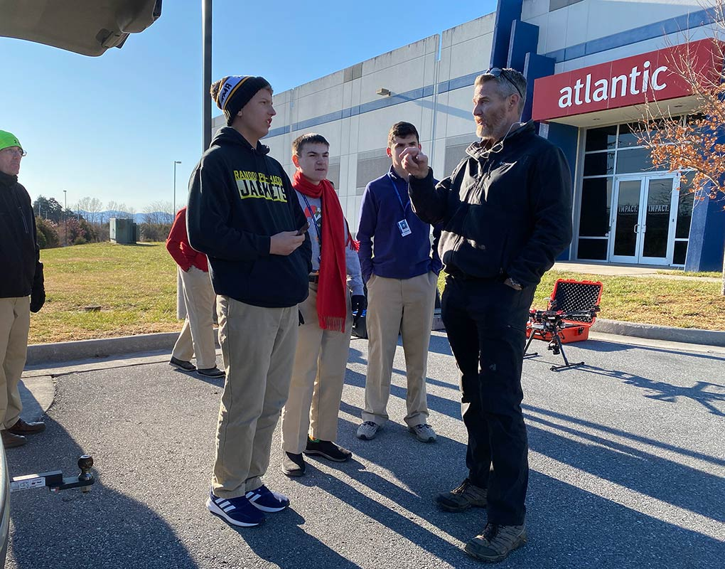 Brian Kelly explains the day's mission to R-MA unmanned flight operations students. Mr. Kelly and the class were asked to use the drones to inspect the roof of a commercial building.